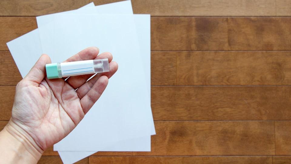 Une main tient un petit étui de plastique dans lequel se trouve un bandelette.