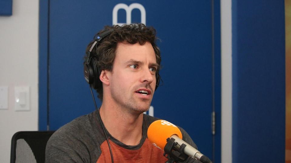 Un homme portant un vêtement gris et rouille parle dans un micro orange.
