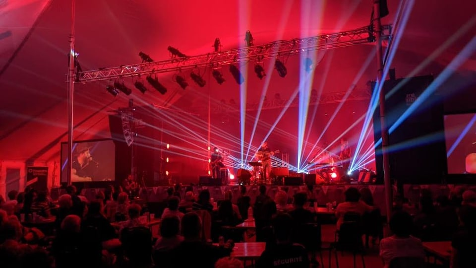 Des gens sur une scène  éclairée par des faisceaux lumineux et le public dans la salle.