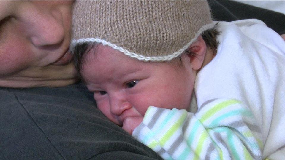 Un bébé naissant est dans les bras d'une femme.