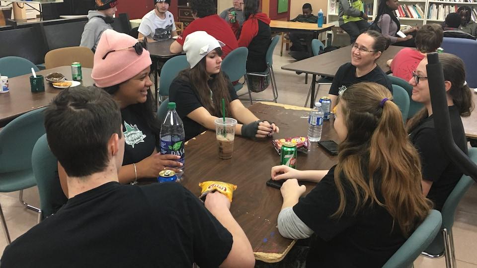 Plusieurs adolescents rassemblés autour d'une table.
