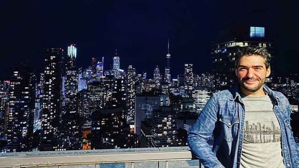 Un homme sourit sur un terasse du centre-ville de Toronto qui surpombe des gratte-ciels.