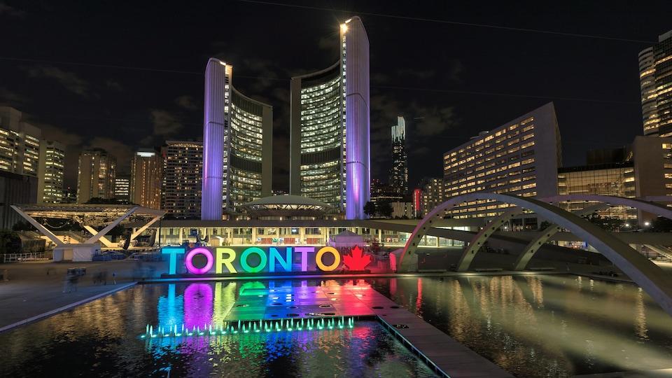 Vue nocturne sur ce grand ensemble architectural marqué par une enseigne lumineuse montrant le mot Toronto.