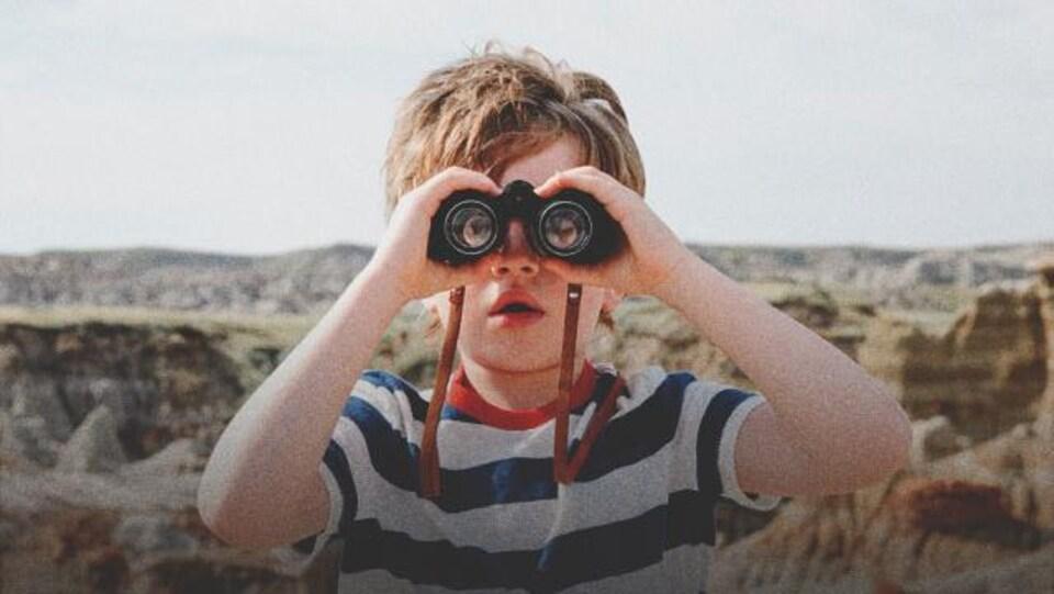 Un jeune garçon tient des jumelles et fait dos à un canyon
