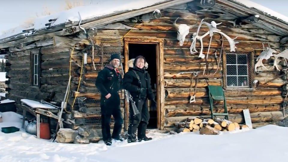 Un homme et une femme posent devant une cabane en bois en hiver.