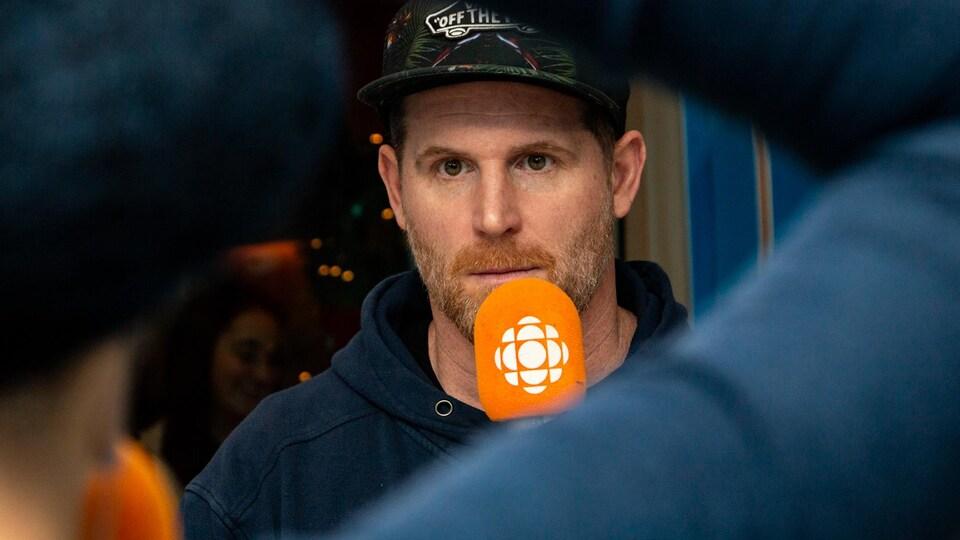 Portant une casquette sombre, le comédien écoute attentivement la question posée par l'animatrice Pénélope McQuade.
