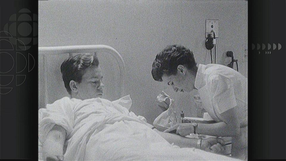 Image en noir et blanc montrant un jeune homme couché dans un lit d'hôpital et une infirmière lui faisant une prise de sang