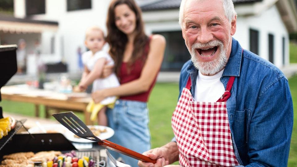 Un homme, une femme et un enfant devant un BBQ.