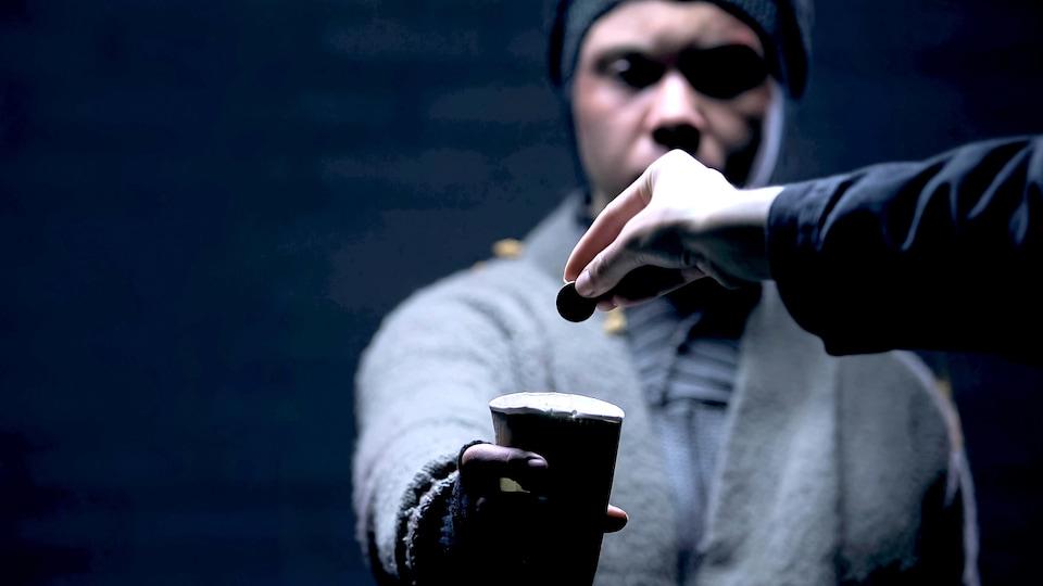 Un jeune homme tend un verre vide alors qu'un passant lui donne de la monnaie.