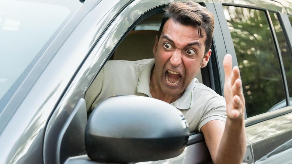 Un homme enragé dans sa voiture.