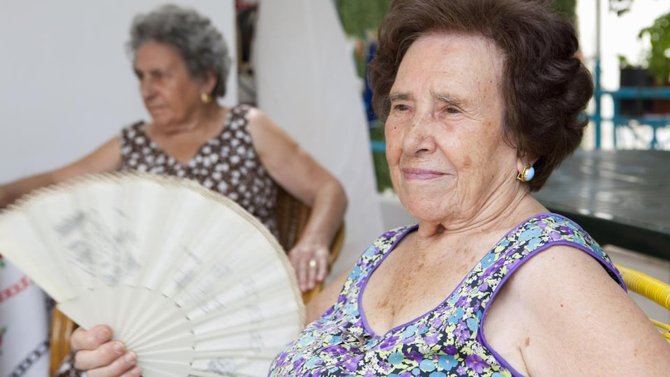 Une femme âgée agite un éventail.