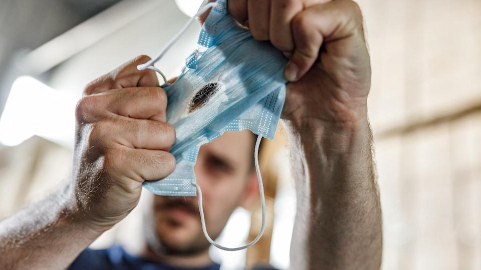 Un homme déchire son masque.