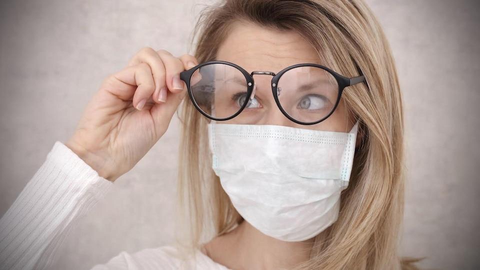 Une femme qui porte un masque regarde la buée dans ses lunettes.