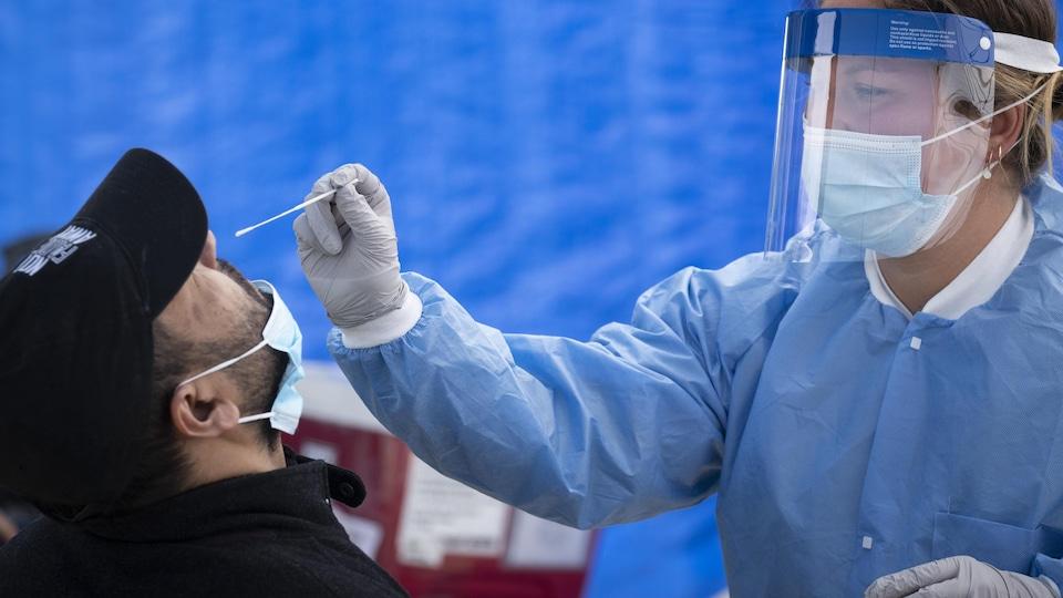 Une professionnelle de la santé effectue un test de dépistage du coronavirus dans une clinique mobile du quartier Saint-Michel.