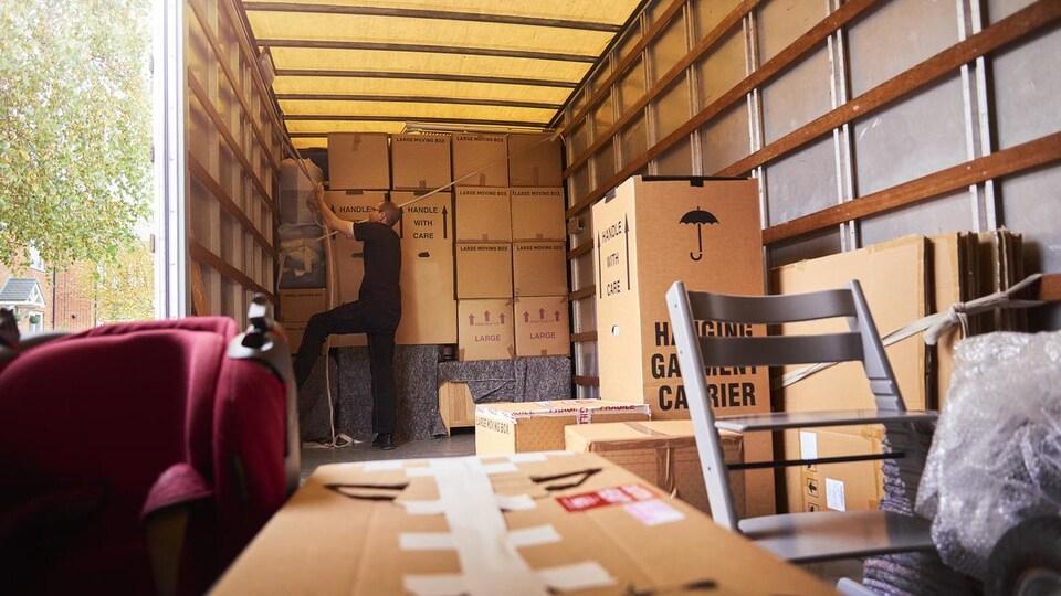 Un homme organise l'intérieur d'un camion rempli de boîtes et de meubles.