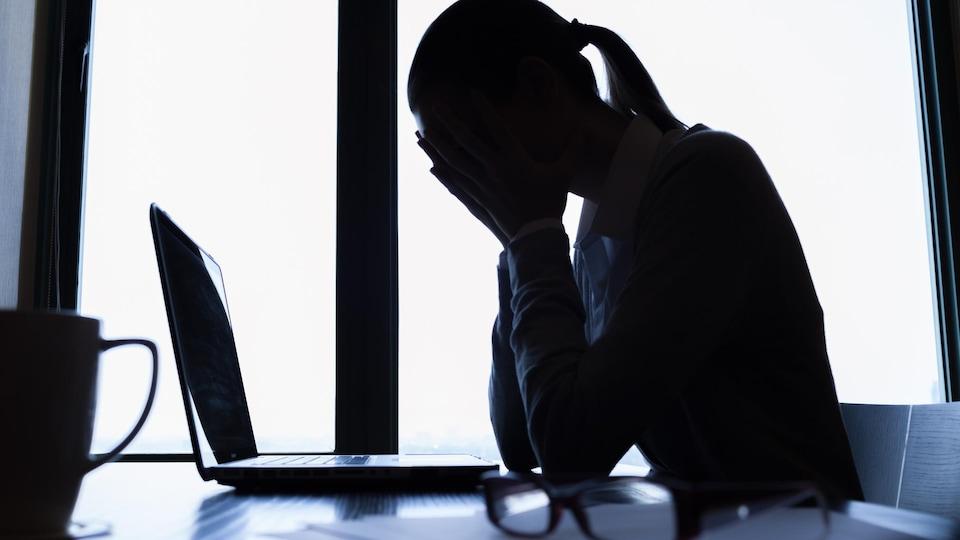 Une femme se tient la tête, assise à son bureau devant un ordinateur.