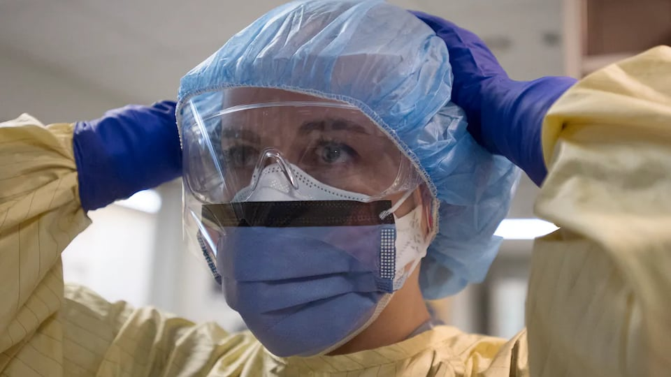 Une femme couverte avec des équipements de protection (masque, lunettes, couvre cheveux, gants et blouse).