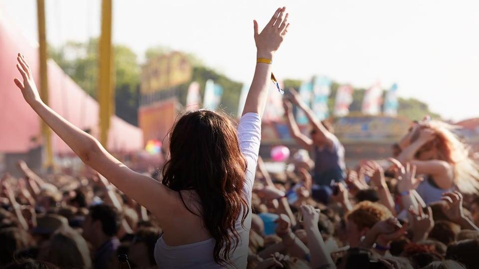 Une femme au-dessus de la foule lève les bras en l'air.