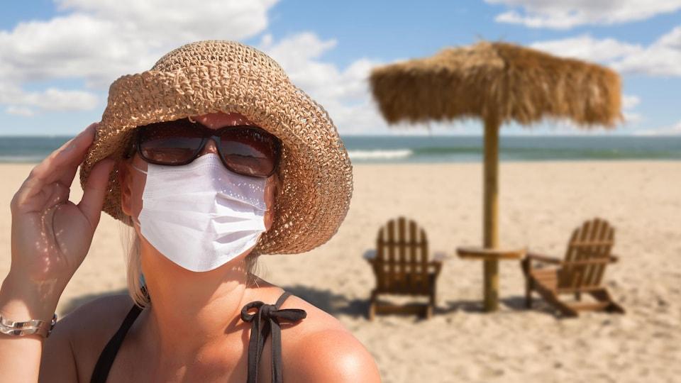 Une femme porte un masque sur la plage.