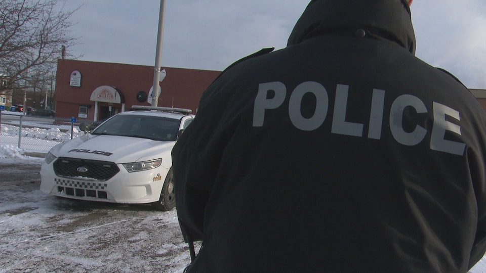 Un policier de dos devant sa voiture.