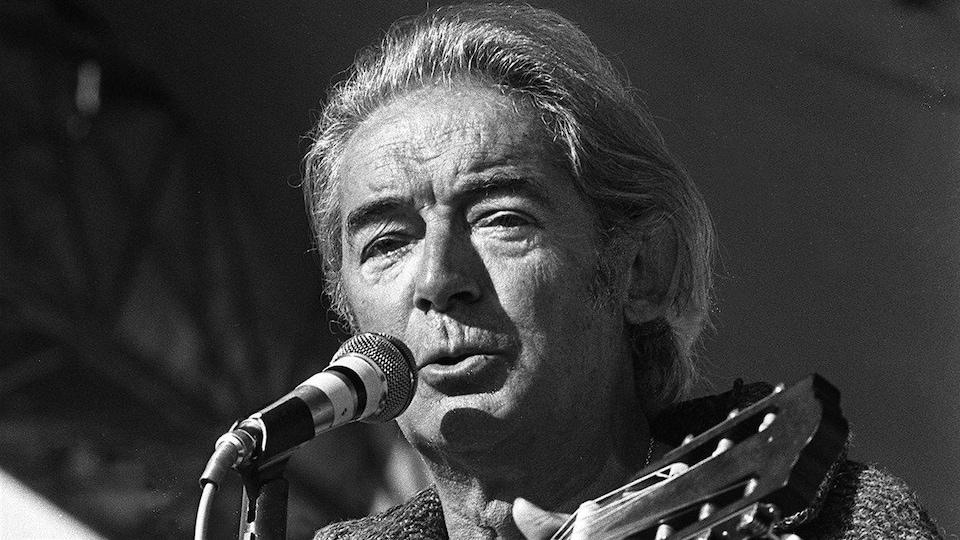Une photo en noir et blanc de l'artiste qui chante devant un micro.
