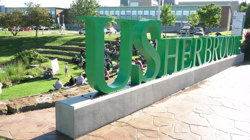 Logo de l'Université de Sherbrooke, et des étudiants suivent un cours en plein air.