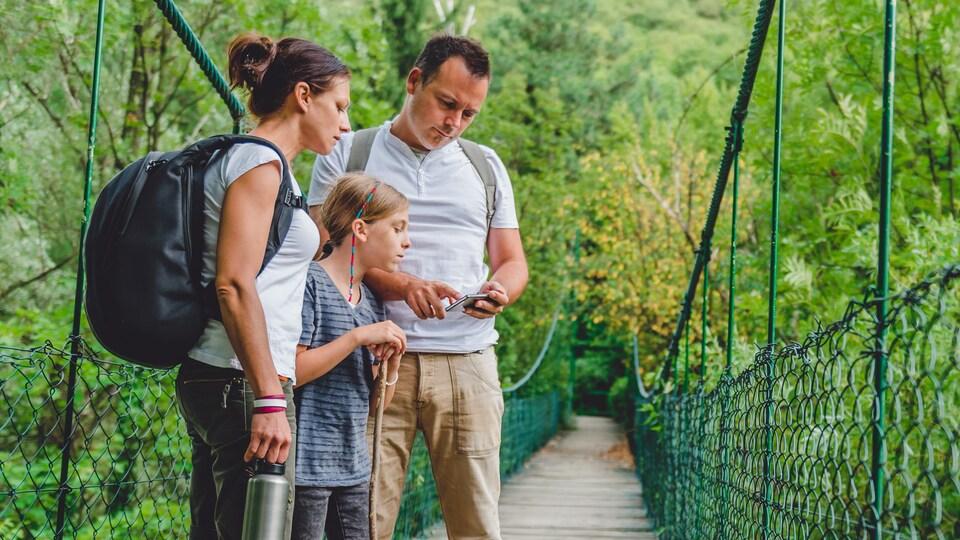 Une famille en randonnée consulte un téléphone intelligent.