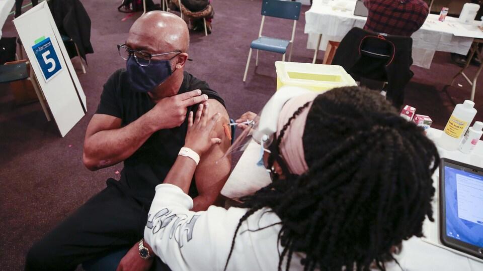 Un homme se fait vacciner par une infirmière.