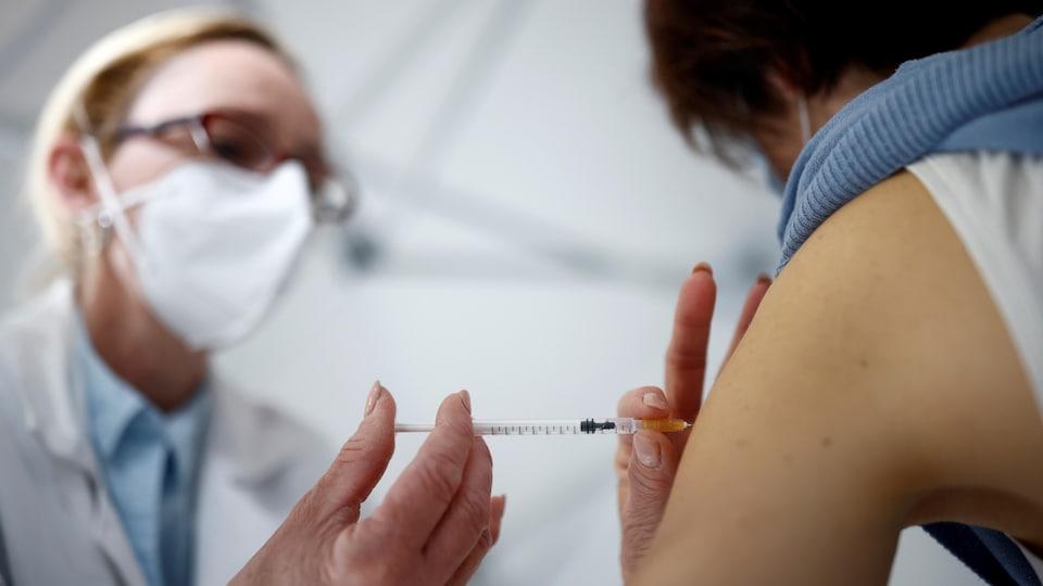 Une infirmière vaccine une personne.