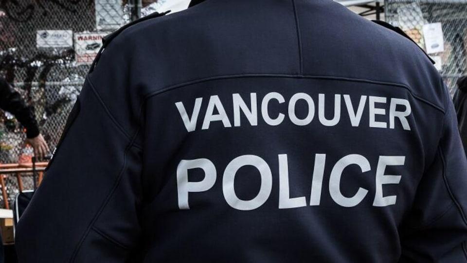 Un homme de dos porte un chandail sur lequel il est écrit Vancouver Police