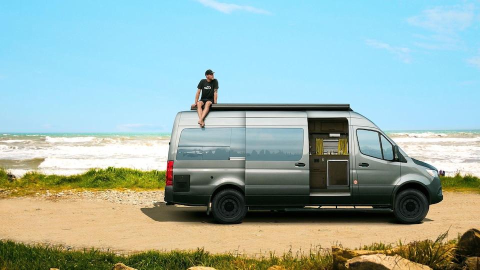 Un homme assis sur le toit d'une fourgonnette stationnée sur une plage, au bord de la mer.