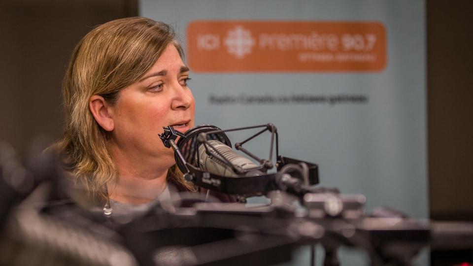 Une femme parle au micro dans un studio.