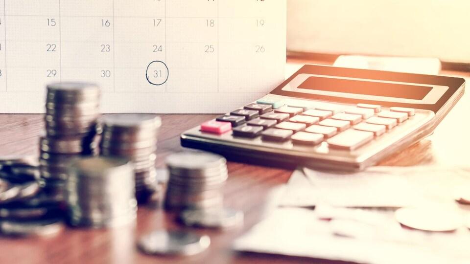 Un calendrier, de la monnaie et une calculatrice sont placés sur une table.