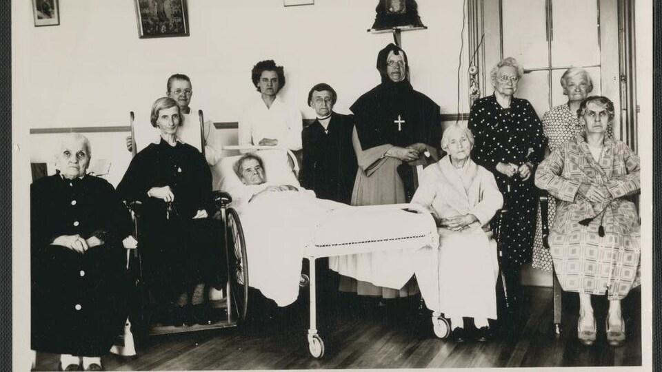 Photo en noir et blanc montrant plusieurs femmes âgées, dont une alitée et une en fauteuil roulant, en compagnie d'une religieuse.