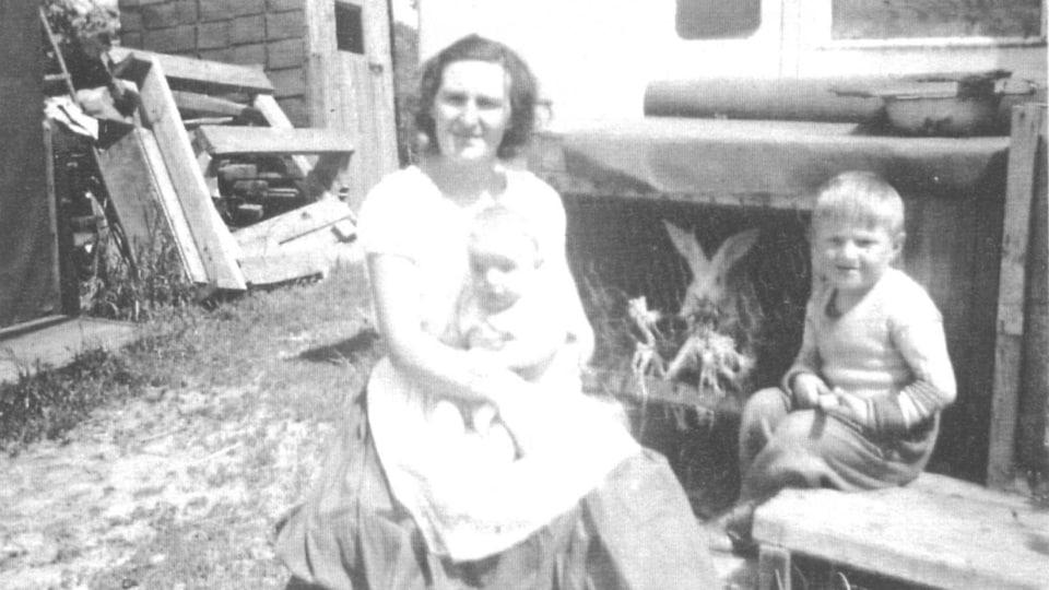 Photo en noir et blanc montrant une mère tenant un bébé et un petit garçon dans une cour où on voit une cage avec un lapin.