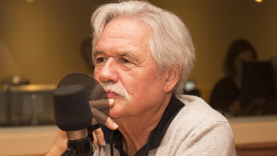 L'homme est devant un micro en entrevue.