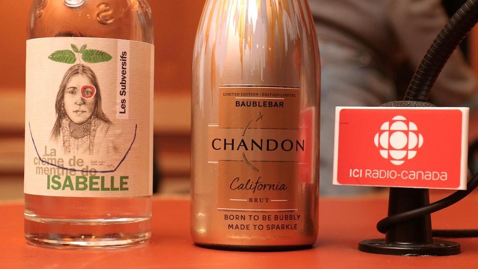 Deux bouteilles de vin posées près d'un pied de micro de radio.