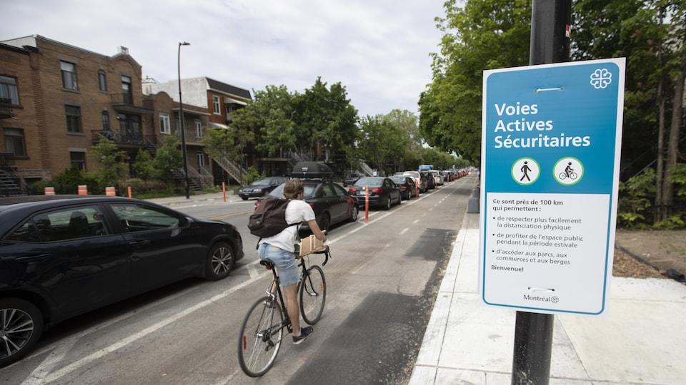 Un cycliste circule sur la voie cyclable de l'avenue Christophe-Colomb. Une pancarte explique le concept de voies actives sécuritaires.