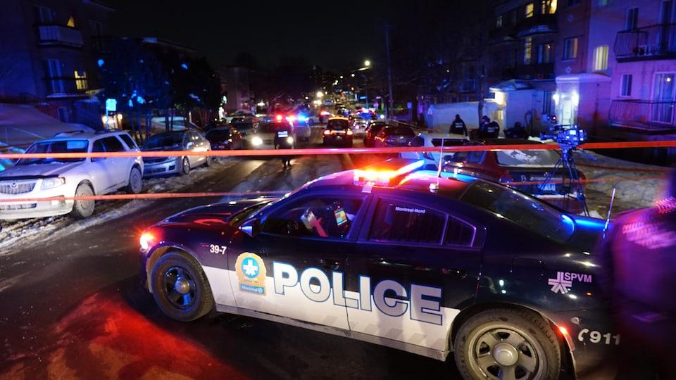 Une voiture de police avec les gyrophares allumés devant un ruban orange désignant le périmètre de sécurité.