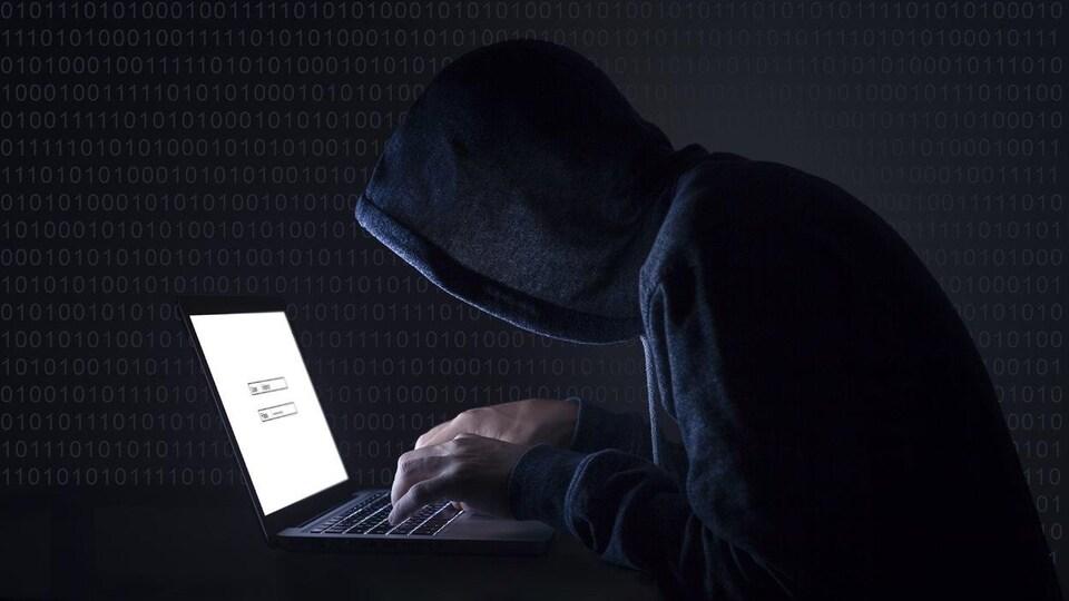 Un homme vêtu d'un kangourou à capuchon noir; il tape sur un ordinateur portable dans le noir.
