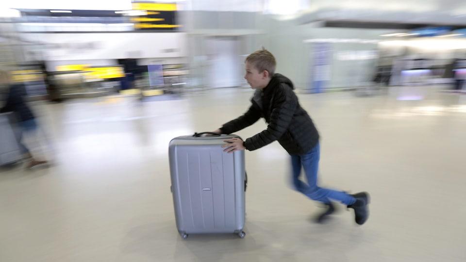 Un enfant pousse sa valise sur roues dans un aéroport.