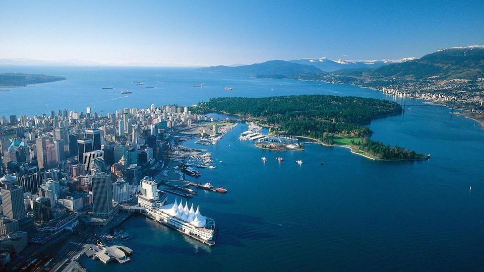 Vue aérienne du Parc Stanley et du centre-ville ouest de Vancouver. On voit des bateaux et les montagnes à l'horizon.