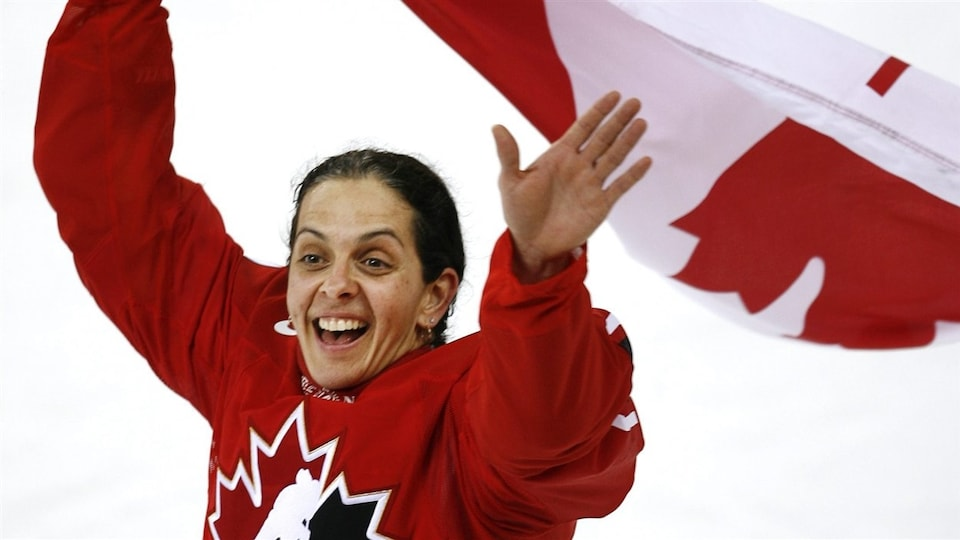 Elle sourit avec le drapeau canadien dans ses mains.