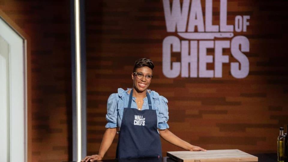 Une femme noire souriante portant un tablier sur le plateau de Wall of Chefs.