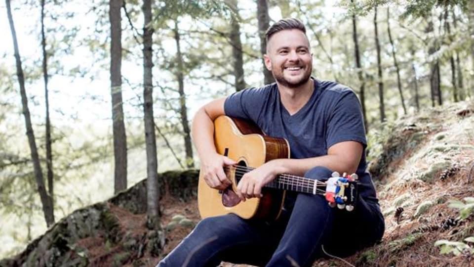 Wilfred LeBouthillier assis en forêt avec une guitare.