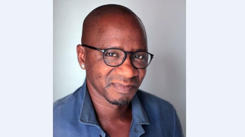 Portrait de l'écrivain Wilfried N'Sondé. Il porte des lunettes cerclées de noir et une chemise bleue.