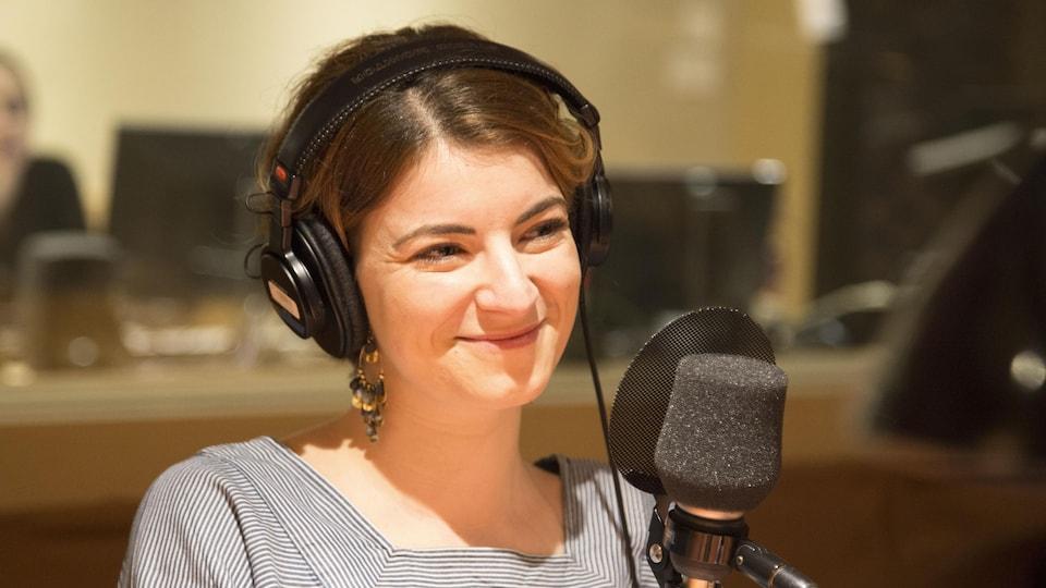 Elle sourit, des écouteurs sur la tête et assise derrière un micro.