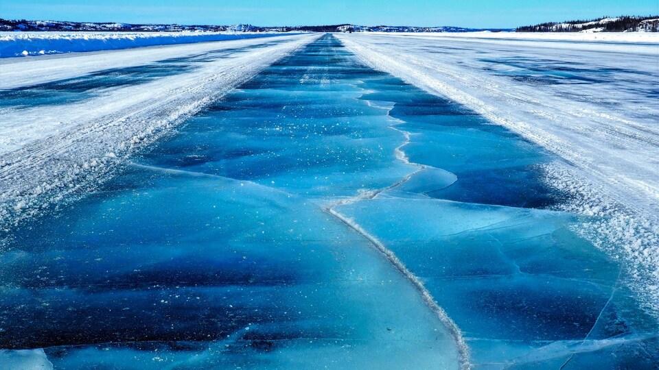 Une route de glace bleue déblayée de sa neige est craquelée.