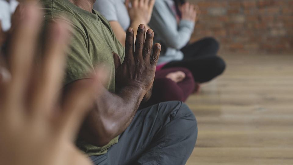 Un homme médite les jambes croisées et les mains jointes dans une classe de yoga.