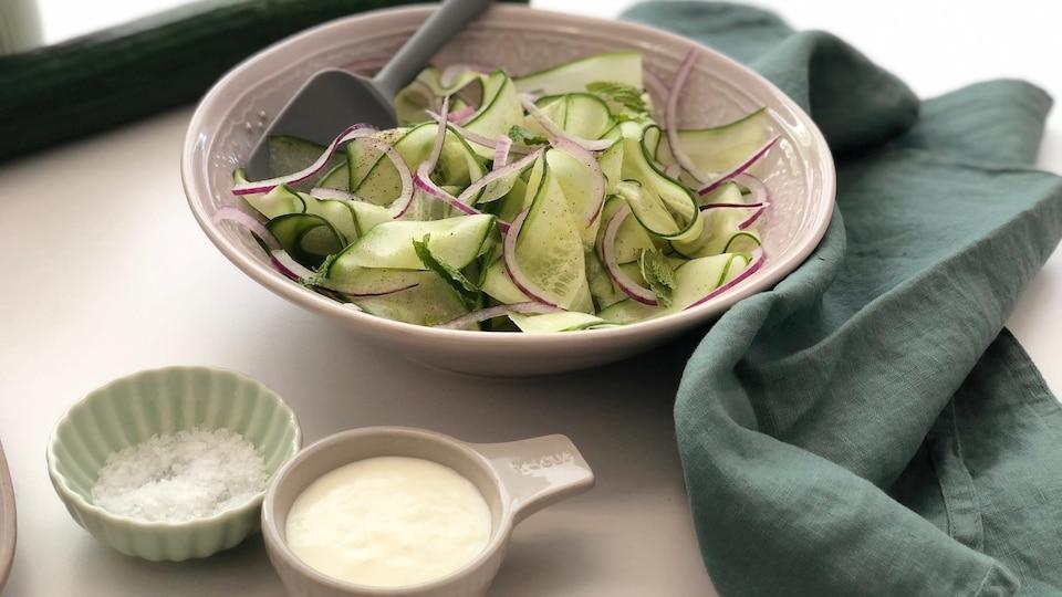 Un bol de salade de concombre en rubans avec un petit bol de vinaigrette à l'ail.